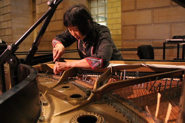 <p>John Cage's music for prepared piano gets its unusual sounds from objects placed between the strings. Margaret Leng Tan prepares a piano at the Philadelphia Museum of Art before her performance of Cage's music for films. (Emma Lee/for NewsWorks)</p>