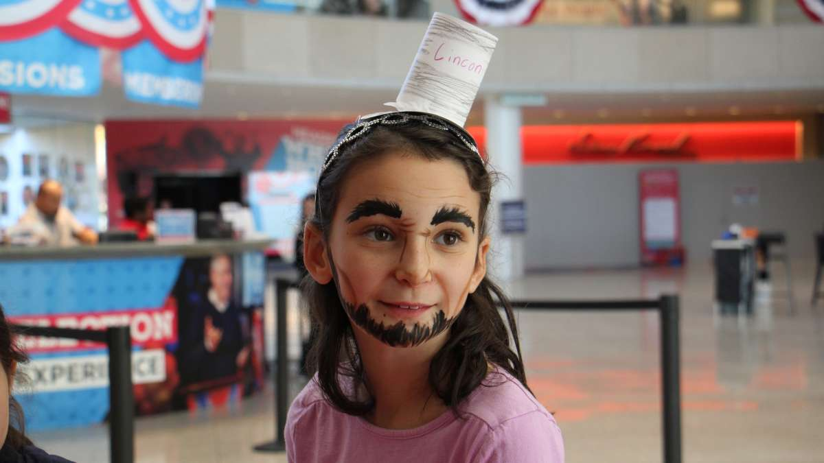 A yount Abraham Lincoln portrayer transforms her appearance with artful face paint during an Election Day visit to the National Constitution Center.