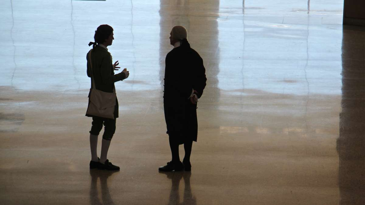 Historic Philadelphia presidential portrayers Sean Connolly (left) and John Lopes talk on the floor of the National Constitution Center's Grand Hall Lobby during Election Day festivities.