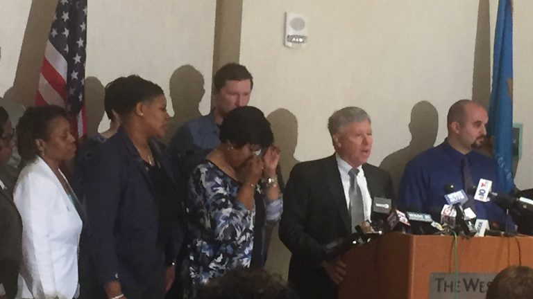 Lt. Steven Floyd's family join attorney Thomas Crumplar announcing a lawsuit against state leaders including former governors Jack Markell and Ruth Ann Minner. (Zoë Read/WHYY)