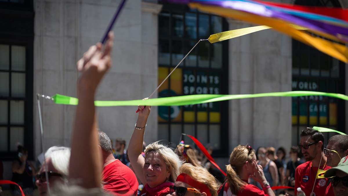 Jan Monaghan and other employees of General Electric wave streamers at Philadelphia Pride Parade and Festival. (Branden Eastwood for NewsWorks)