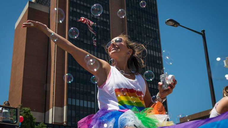 Erin Cooper is surrounded by bubbles while riding on the Zip Car float at Philadelphia Pride Parade and Festival. (Branden Eastwood for NewsWorks)