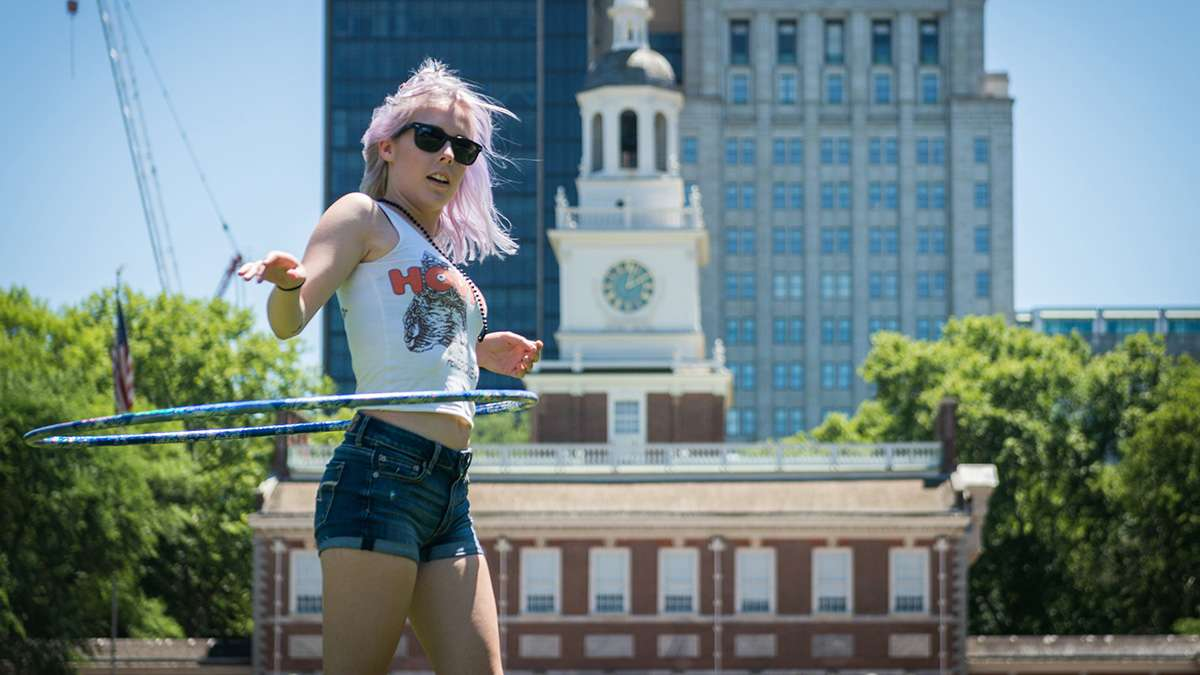 Katie Schwald dances with a hula hoop in front on independence hall at Philadelphia Pride Parade and Festival. (Branden Eastwood for NewsWorks)