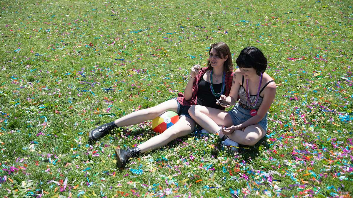 Laura Foley and Ella Anderson sit in confetti filled grass near Independence Hall. (Branden Eastwood for NewsWorks)