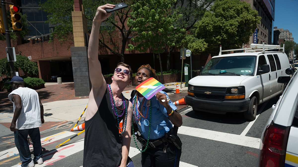 Jamecia Pierce of the Philadelphia Police Department poses for a selfie along the Pride parade route. (Branden Eastwood for NewsWorks)