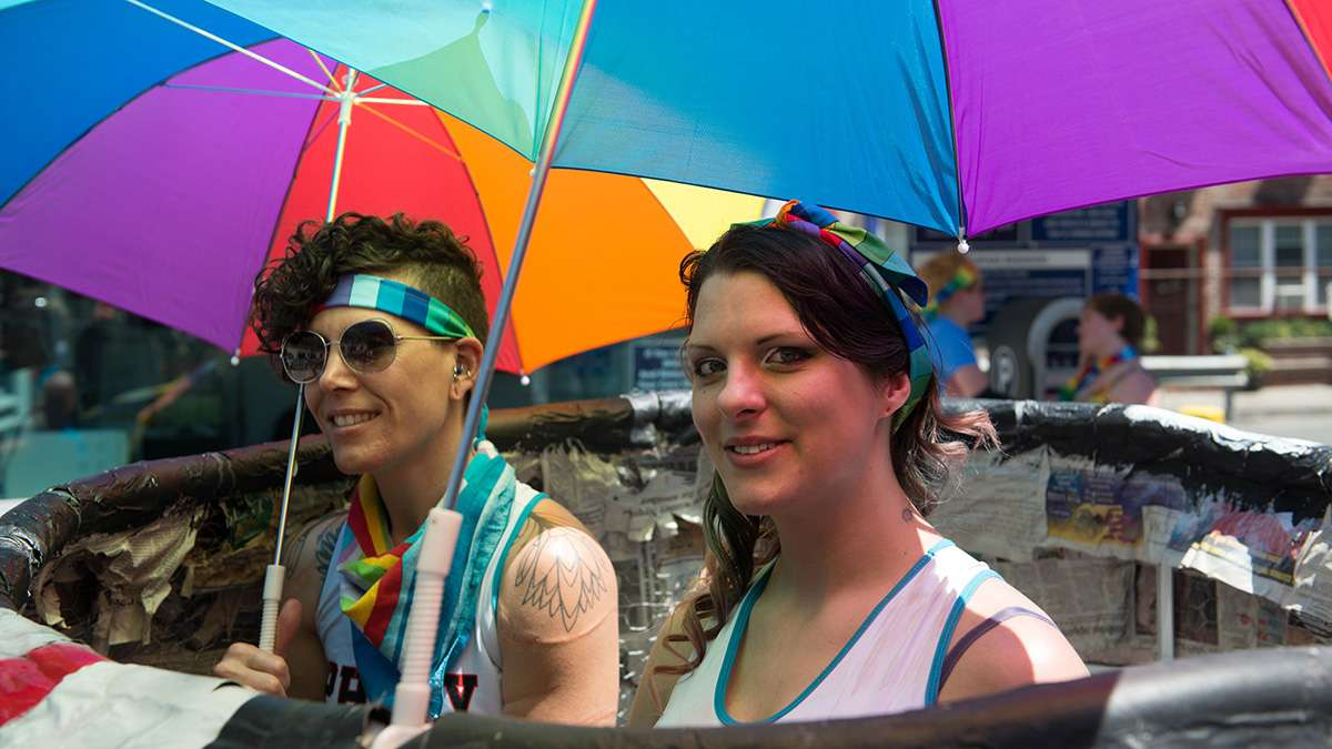 Mishel Castro (left) and Leah Yancoskie pose for a photo near Locust Street while participating in the Philadelphia Pride Parade and Festival. (Branden Eastwood for NewsWorks)