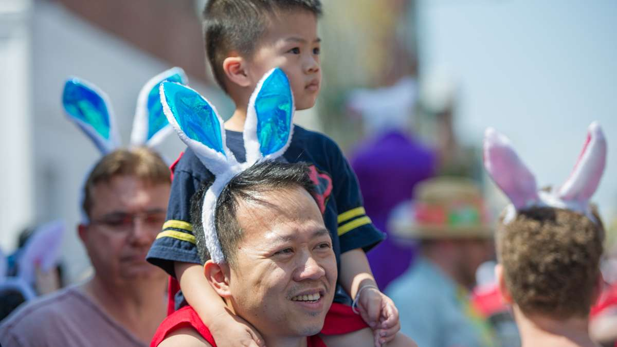 Benjamin Nguyen holds his son, Levi, aloft to view the parade.