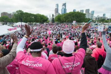 Participants in the Survivors Parade of Pink and Salute to Forever Fighters wave to supporters on Eakins Oval during the Susan G. Komen Race for the Cure event.