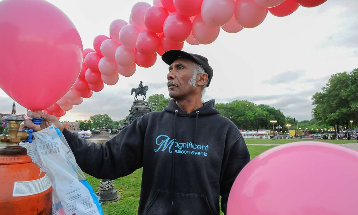 Noel Murray blows up balloons for the balloon arches that cancer survivors walk through on the steps of the Philadelphia Museum of Art.