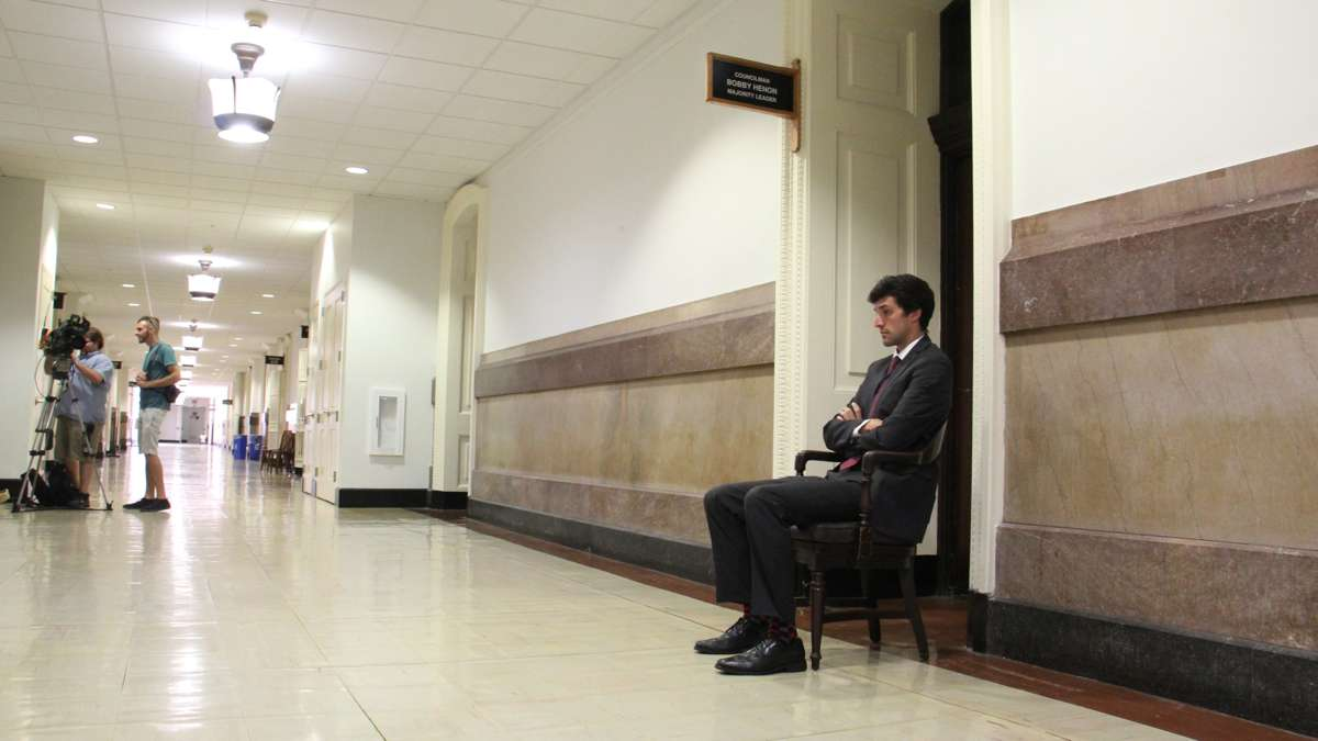 An FBI agent sits guard in front of the City Hall office of Councilman Bobby Henon. (Emma Lee/WHYY)