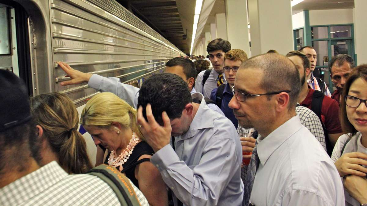 Boarding passengers form a crush at the door to a regional rail car during the evening commute. (Emma Lee/WHYY)