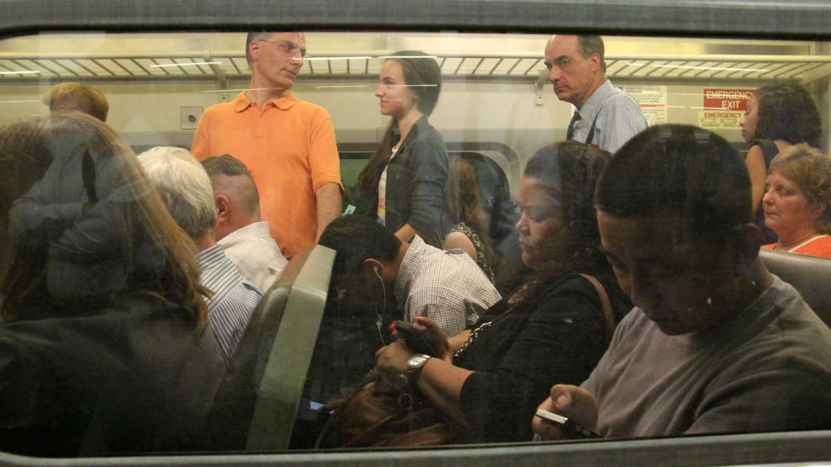 Passengers sit three to a seat and fill the aisles on a SEPTA regional rail car. (Emma Lee/WHYY)