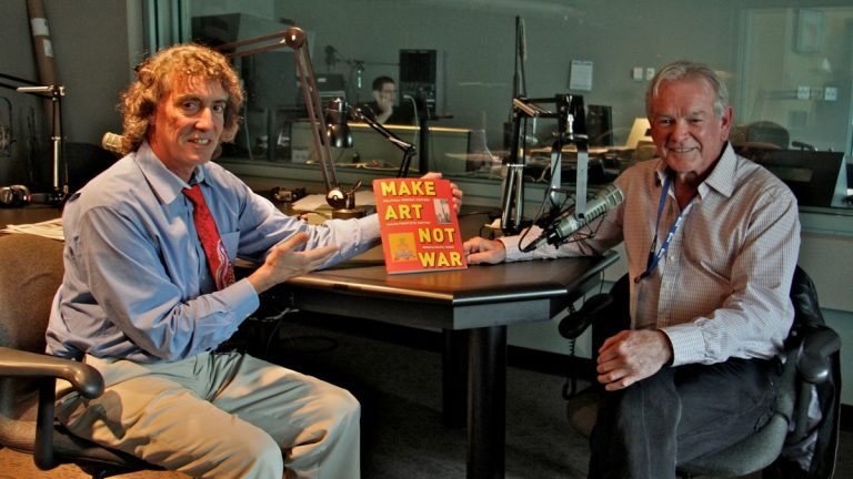 Dave Heller and Ralph Young at WHYY studios with Young's book, 'Make Art, Not War: Political Protest Posters from the 20th Century.' (Emma Lee/WHYY)