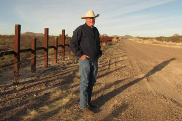 Bill McDonald, rancher conservationist and Executive Director of the Malpai Borderlands Group, stands at the U.S./Mexico border near Douglas, Arizona  (Maya Springhawk Robnett/for WHYY)