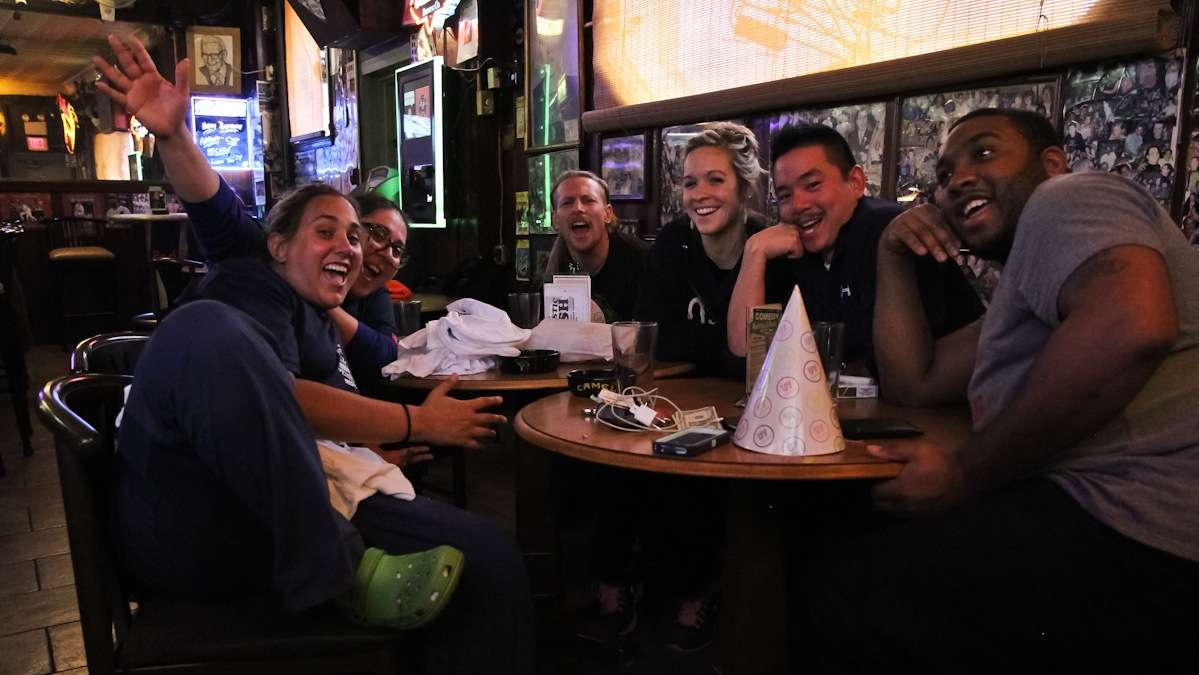 Nurse Mary-Jo Athena Metaxas (second from left) is at the bar 'post shift after saving lives.' She came with her coworkers to unwind and eat a Pat's cheesesteak for breakfast. (Kimberly Paynter/WHYY)
