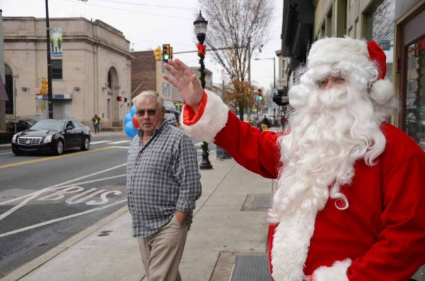 <p><p>Santa Claus waves to pedestrians and drivers along Ridge Avenue. (Jimmy Viola/for NewsWorks)</p></p>