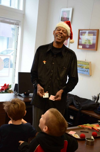 <p><p>Lamont Samuel, also known as Mr. Magic, shares a laugh with children attending RDC's holiday party on Saturday. (Jimmy Viola/for NewsWorks)</p></p>