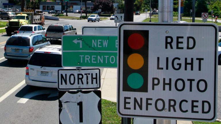 A red light photo enforcement sign is seen below a red light camera on Franklin Corner Road in Lawrence Township, Wednesday, July, 25, 2012. (AP Photo/Mel Evans)