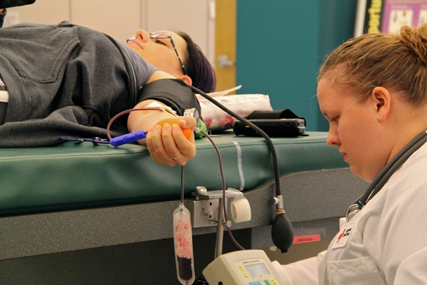 <p>Donor collection assistant Bonnie Merrylees keeps an eye on things as Orli Gal donates a pint of blood at the Red Cross donation center in Philadelphia. (Emma Lee/for NewsWorks)</p>