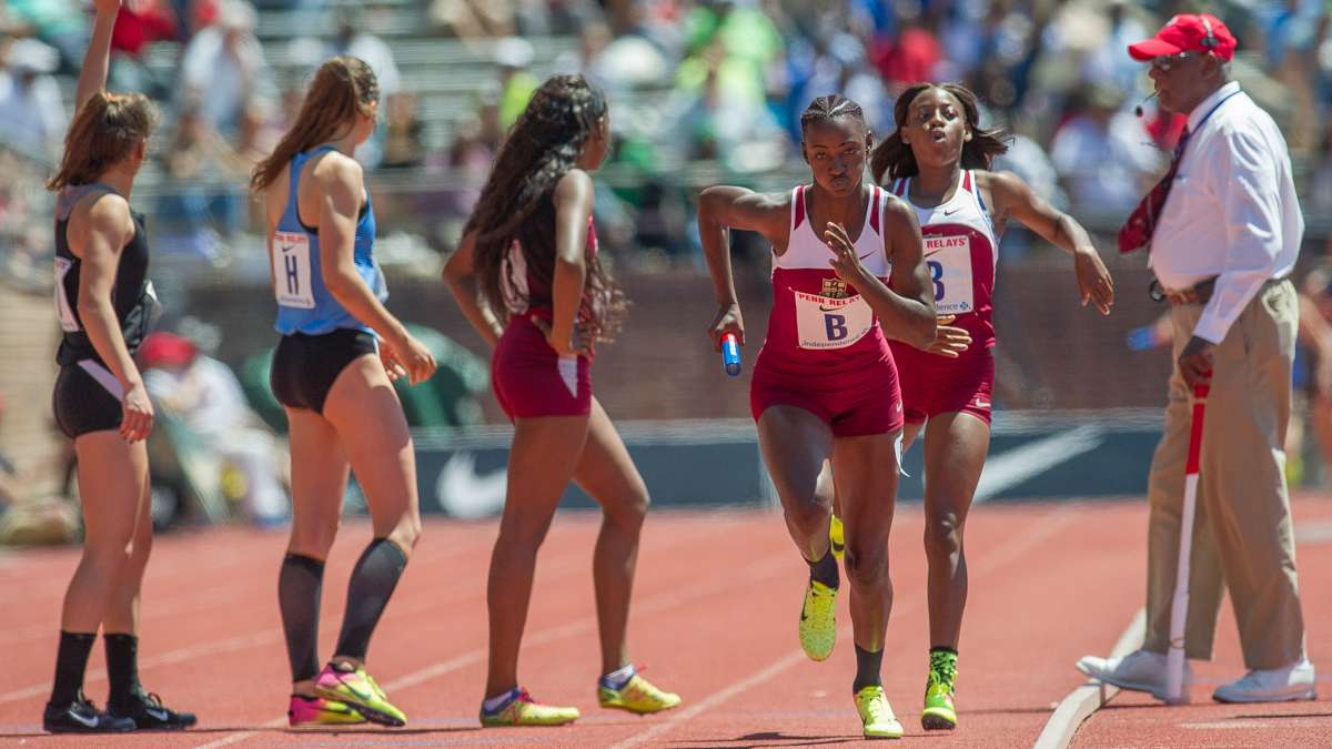 Edwin Allen's Shellece Clarke passes the baton to Patrice Moody in the anchor leg of the high school girls' 4-by-100 Championship of America. The team from Clarendon, Jamaica, won the race with a Penn Relays record time of 43.96 seconds.