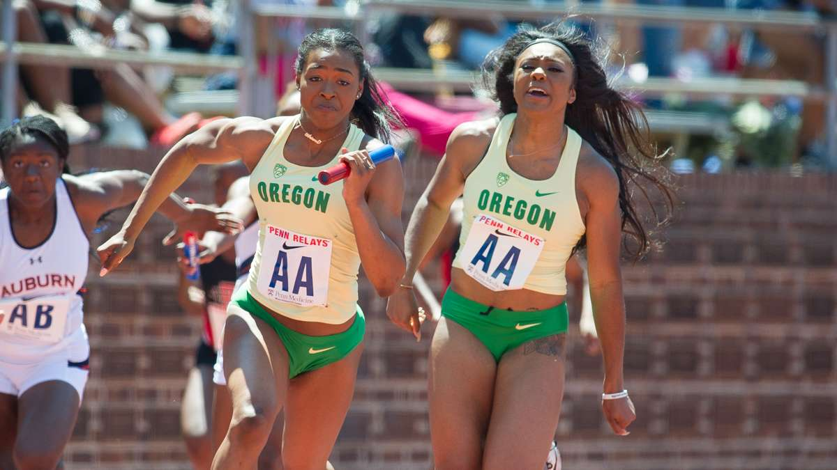Oregon's Ariana Washington takes the baton from Makenzie Dunmore to win the college women's 4-by-100 Championship of America in 42.35 seconds.