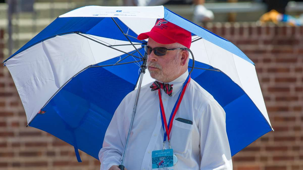 With temperatures in the mid-80s, long and triple jump official Eric J. Miller keeps the sun off.
