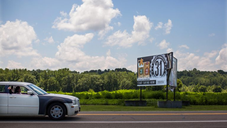 A billboard advertises discounted cigarettes adjacent to a field used to grow tobacco on the Seneca Nation's Cattauragus reservation in Western New York. (Photo by Jessica Kourkounis/for WHYY)