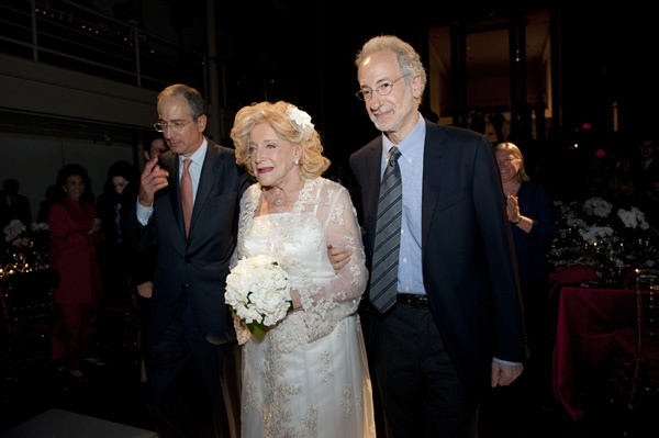 "<p><p>Suzanne Roberts is escorted ""down the aisle"" by her two sons, Brian (left) and Rob Roberts (Photo courtesy of Susan Beard Design)</p></p>"
