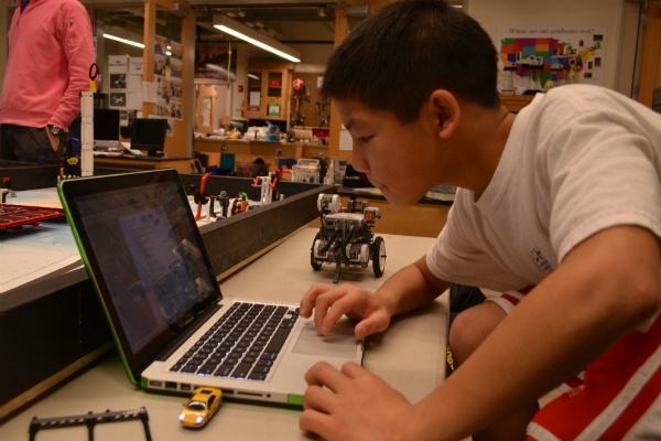 <p><p>Programming the boys' robot for Saturday's robotics competition. (Zachary Shevich/for NewsWorks)</p></p>
