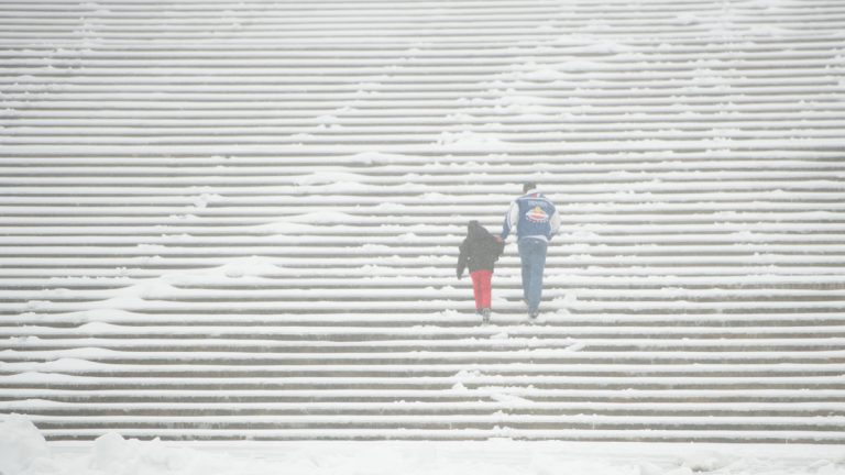 Snow and sleet did not deter two members of the Huerta family, visiting from Houston, from running up the Rocky steps during the winter storm in Philadelphia on Tuesday, March 14, 2017. (Jonathan Wilson for Newsworks)