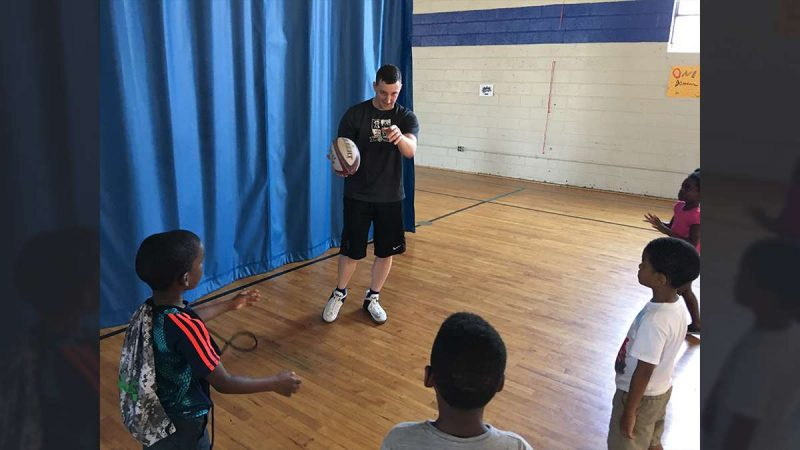 Program coordinator Dave Codell teaches a lesson on passing during a Rugby camp at the Northeast Frankford Boys & Girls Club (Jay Scott Smith/WHYY)