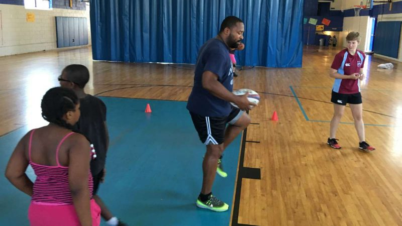 Rugby coach James Brunson demonstrates footwork to a group of kids during a Rugby camp at the Boys and Girls Club in North Frankford. (Jay Scott Smith/Newsworks)