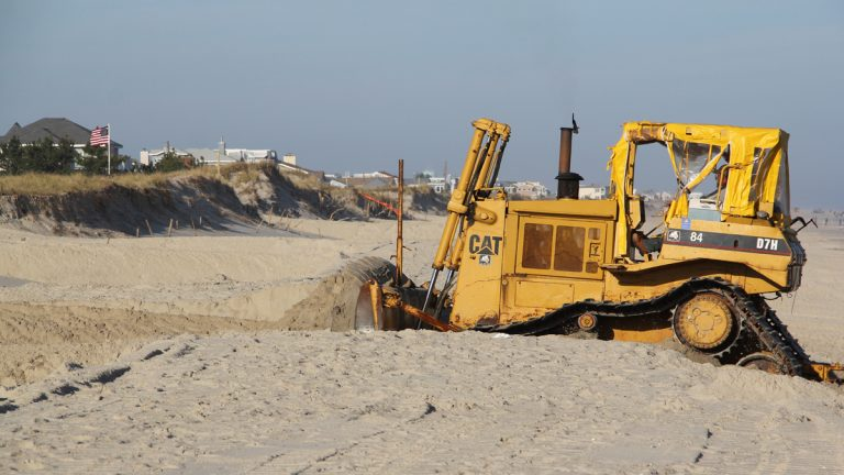 A bulldozer on Long Beach Island moves sand to restore the dunes that were swept away by Hurricane Sandy. (Emma Lee/for NewsWorks)