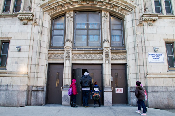 A parent walks his children into school at John L. Kinsey Elementary in North Philadelphia. The school is one of many on a list of Philadelphia Public Schools that the district plans to close at the end of the school year. (Brad Larrison/for NewsWorks)