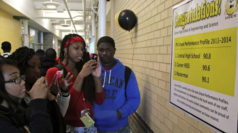 This 2014 photo shows students at Carver High School in Philadelphia stopping in the hall to photograph a poster detailing the new state rankings that place their school at No. 2 in the district. (Emma Lee/WHYY)