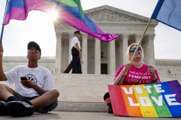 Carlos McKnight, 17, of Washington, (left), and Katherine Nicole Struck, 25, of Frederick, Md., hold flags in support of gay marriage as security walks behind outside of the Supreme Court in Washington, Friday June 26, 2015. (Jacquelyn Martin/AP Photo)
