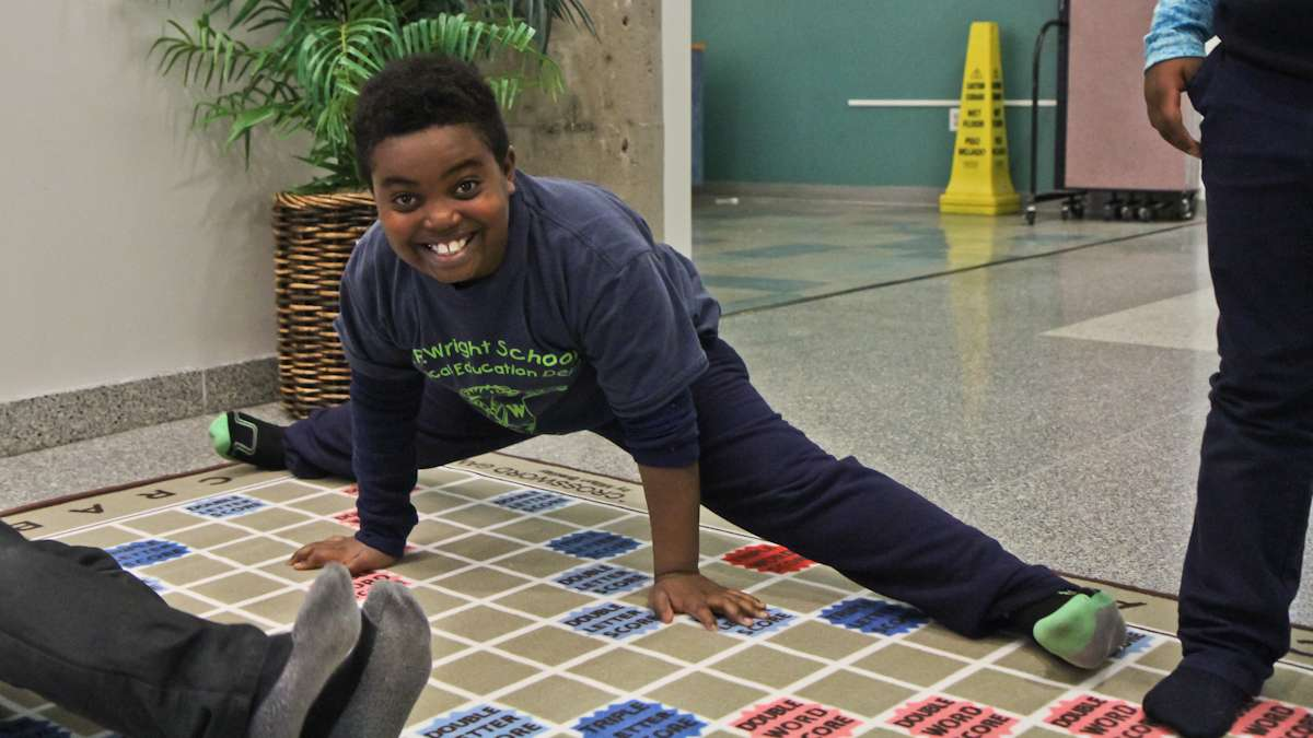 Nathaniel Rapley, 9, takes a break from playing to stretch on the scrabble rug. (Kimberly Paynter/WHYY)