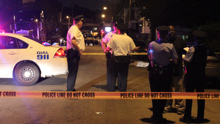 Police on the scene of Friday night's fatal shooting on East Walnut Lane. (Matthew Grady/for NewsWorks)
