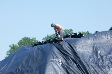 A worker installs black protective tarps during this hot summer heat in Camden, N.J. (Nat Hamilton/for NewsWorks)