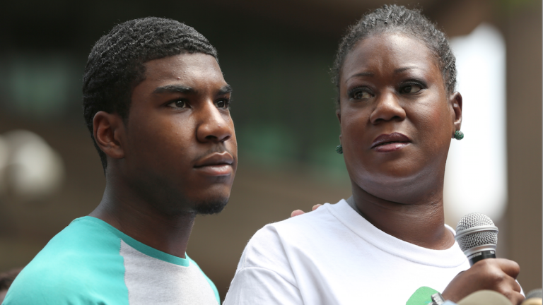 Sybrina Fulton, mother of Trayvon Martin, is joined by her son Jahvaris Fulton as she speaks to the crowd during