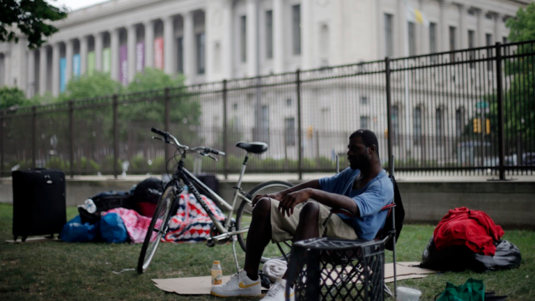 Terrell Caldwell, who has been homeless for four years, sits among his possessions in view of the Free Library of Philadelphia where Mayor Michael Nutter announced an anti-poverty plan called