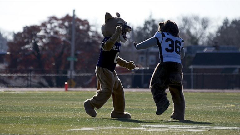 Mascots from MLK High and the since closed Germantown High do battle on the field during the teams' Thanksgiving game last year. (Bas Slabbers/for NewsWorks)