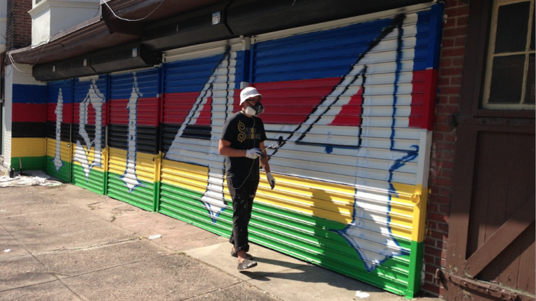 Tim Walkiewicz paints the outside of the yet-opened Coulter Street Supply Co. espresso bar. (Brian Hickey/WHYY)
