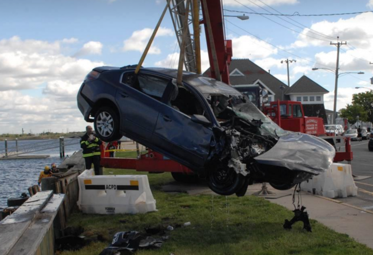 A crane moving a car back to land on Sunday after it was pulled from a bay in Atlantic City. ACPD photo.