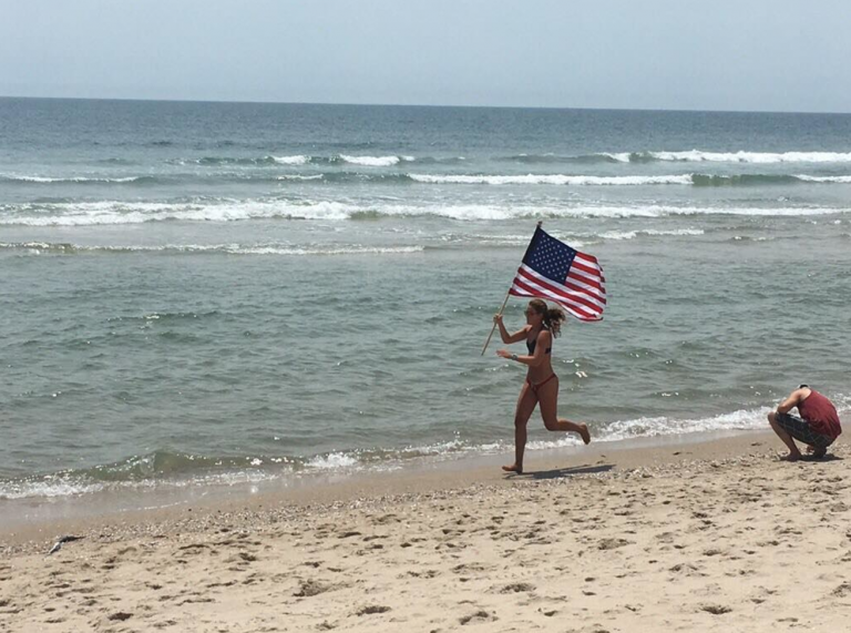 A lifeguard runs the American flag along the shoreline in Long Beach Island. (Image courtesy of Bobby Lynch/Brant Beach Surf Rescue)