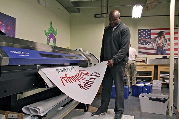 <p>Keith Leaphart, owner of Replica print shop in Center City, watches as a window sign emerges from the printer. (Emma Lee/for NewsWorks)</p>