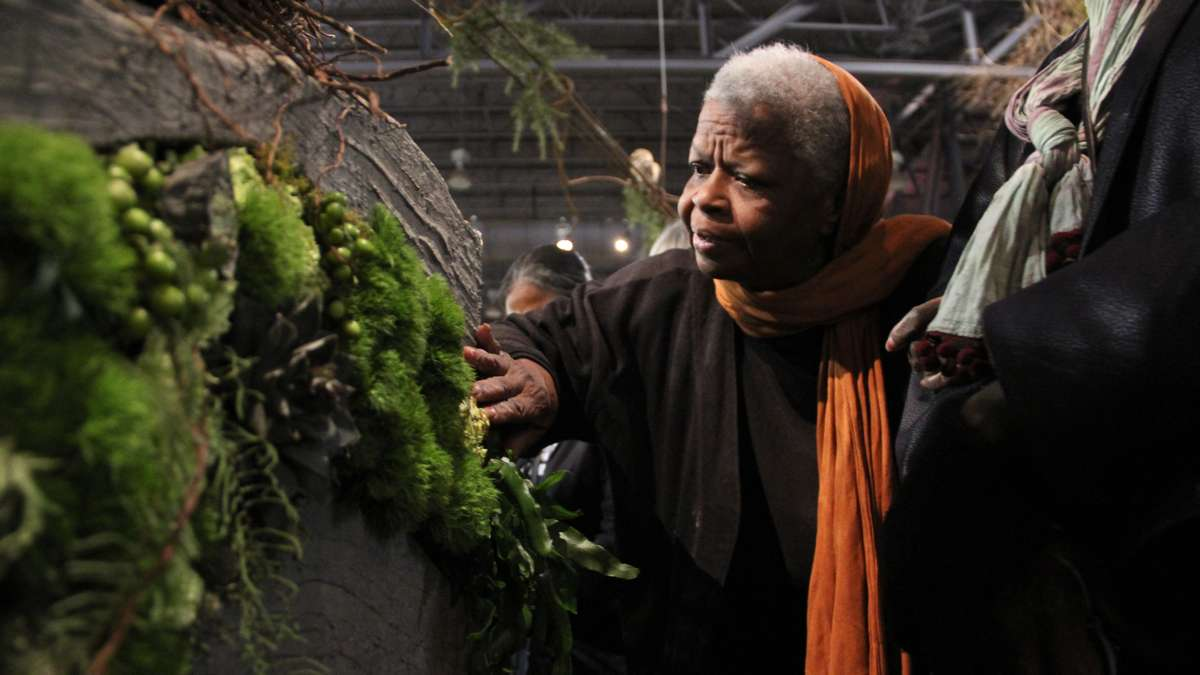 Eleanor Childs runs her fingers along a moss-covered wall during a tour for the blind at the Philadelphia Flower Show.