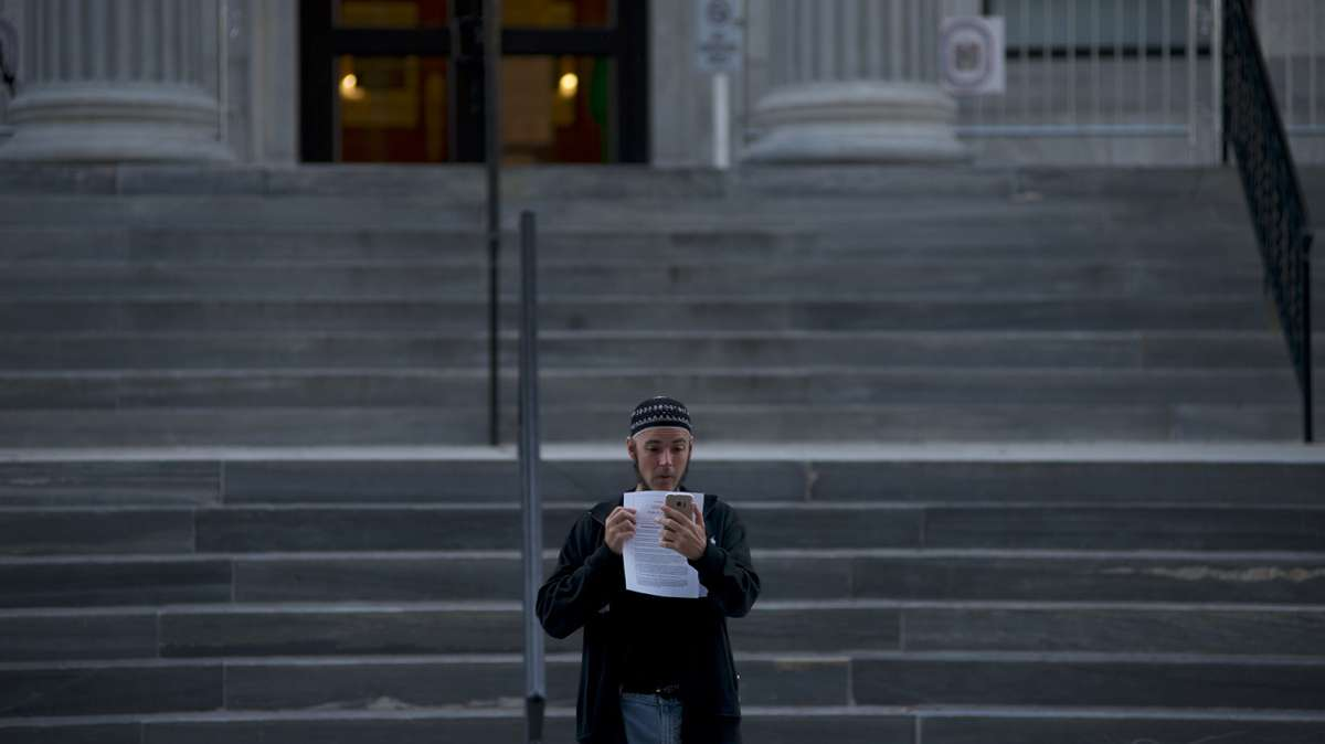 Ahead of the Oct. 24, 2016, sentencing of Former Pennsylvania Attorney General Kathleen Kane, Jonathan Lee Riches, is seen taking a photo of a courtroom public pass, as he stands on the steps of Montgomery County Court House, in Norristown, Pennsylvania. (Emma Lee/WHYY)