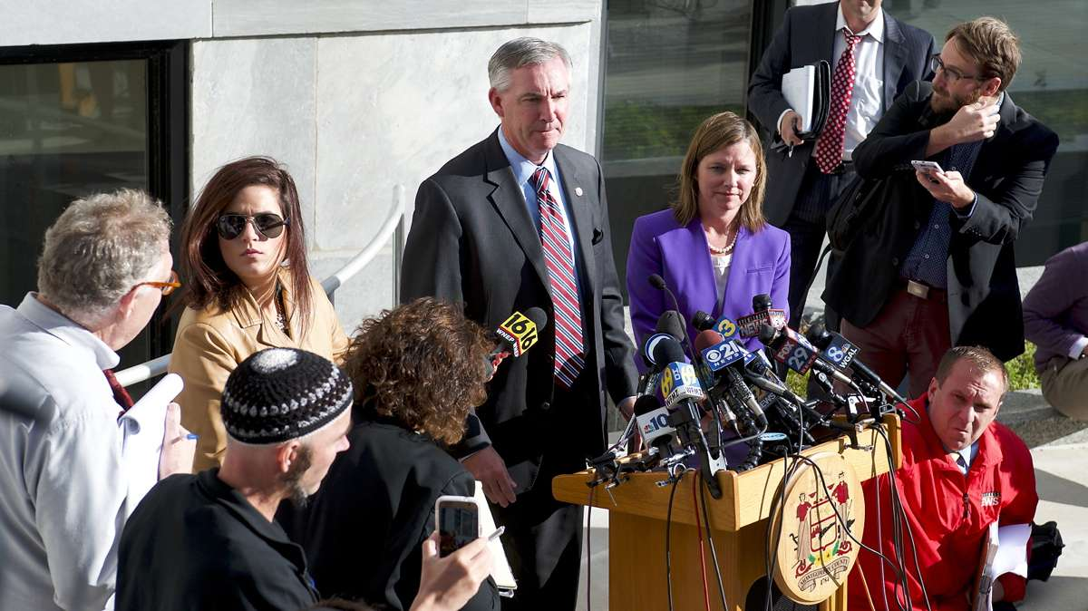 Jonathan Lee Riches is seen in the foreground (left) as Montgomery County District Attorney Kevin Steele talks to the media after former Pennsylvania Attorney General Kathleen Kane received a 10 to 23 months sentence, on Oct.24, 2016, at Montgomery County Court House. (Bastiaan Slabbers for NewsWorks)