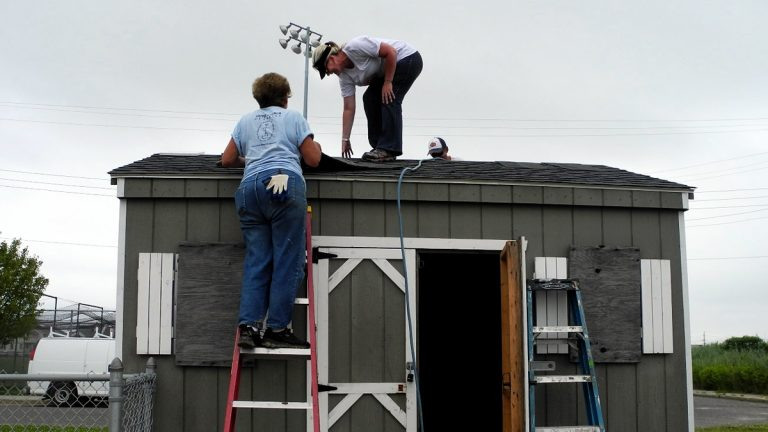 Chrissy Roche helps to rebuild the roof of a ball-field shed in Ventnor, N.J. She says volunteering helps ease the stress and frustration she feels as she rebuilds her own home, which flooded during Superstorm Sandy. (Tracey Samuelson/WHYY)